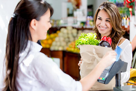 Woman at the local markets checkout paying by debit card